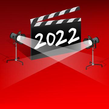 Un clap de cinéma sur un fond rouge avec l'inscription 2022. Il est éclairé par deux projecteurs pour présenter les différents événements cinématographique de la nouvelle année.