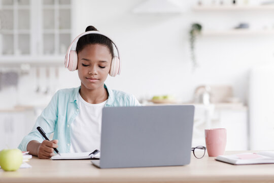 Happy busy teen black girl in earphones studying, doing homework at table with laptop in kitchen interior