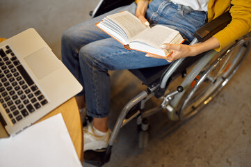 Fototapeta Disabled female student holds a book, top view obraz