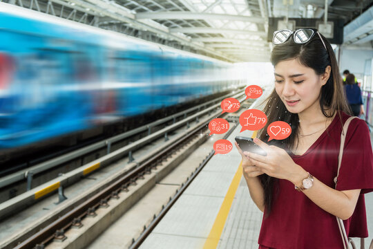 Asian woman passenger using mobile phone to check social network application with number of Like, Love, comment, people and fovorite icon in the Skytrain rails or subway in city, Social media concept,