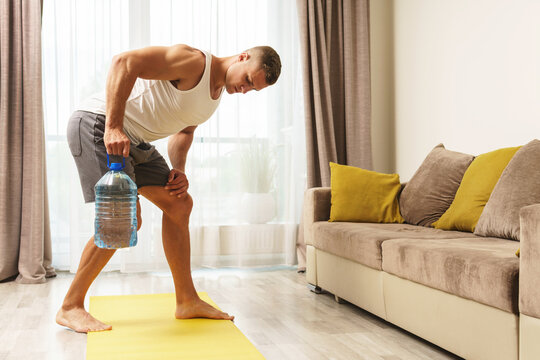 Young athletic man using big bottle of water for home workout