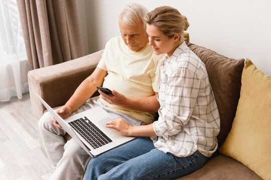 Woman explaining to elderly man how to use laptop and smatphone