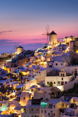 Oia village, Santorini, Greece. View of traditional houses in Santorini. Small narrow streets and rooftops of houses, churches and hotels. Landscape during sunset. Travel and vacation photography.