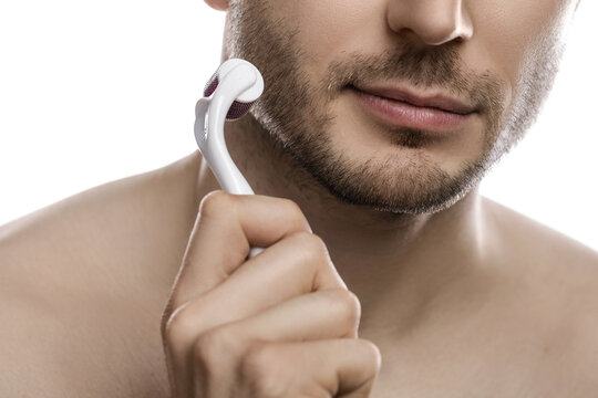 Young handsome man is  using derma roller for beard growth