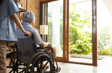Fototapeta Attractive young Asian female nurse kneeling beside senior patient in wheelchair talking, smiling and cheering up in comfort at home.He survive from cancer . obraz