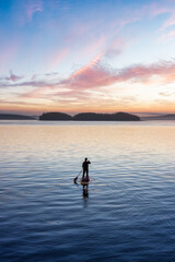 Obraz Adventurous Caucasian Adult Woman on a Stand Up Paddle Board is paddling on the West Coast of Pacific Ocean. Sunny Sunrise Sky Art Render. Victoria, Vancouver Island, BC, Canada. - fototapety do salonu