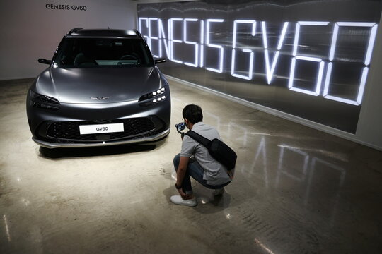 A member of the media takes a photograph of a Genesis GV60 electric vehicle during its showcase in Seoul