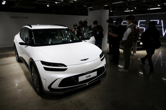Members of the media take photographs of a Genesis GV60 electric vehicle during its showcase in Seoul