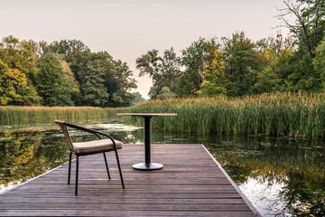 Fototapeta krzesło i stolik na pomoście nad jeziorem jako relaks obraz
