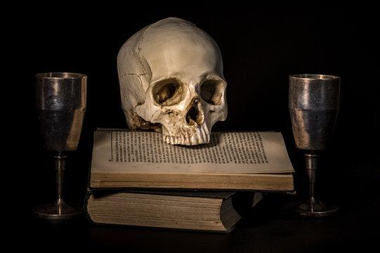 ludzka czaszka na książce i dwa metalowe kielichy na czarnym tle