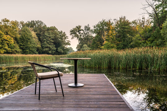 krzesło i stolik na pomoście nad jeziorem jako relaks