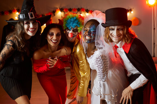 Adult friends having fun at Halloween party. Group shot of happy people dressed up in spooky costumes of witch, devil, clown, corpse bride and vampire standing together, looking at camera and smiling