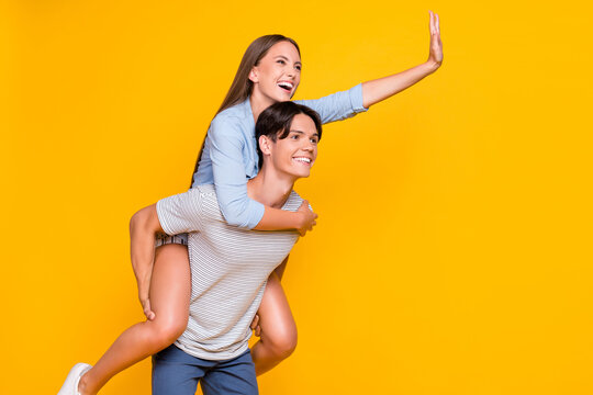 Portrait of attractive cheerful couple piggy backing having fun good mood waving hello isolated over vivid yellow color background