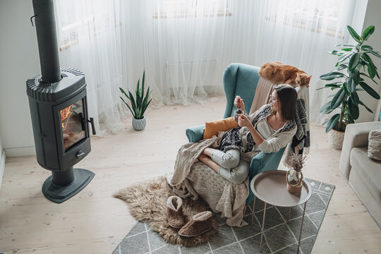 Young woman in a cozy armchair and a plaid sitting by the fireplace with a domestic cat, drinking tea at home