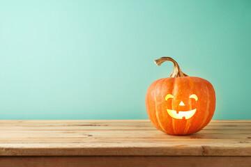 Fototapeta Halloween jack o lantern pumpkin decoration on wooden table. Copy space for product display obraz