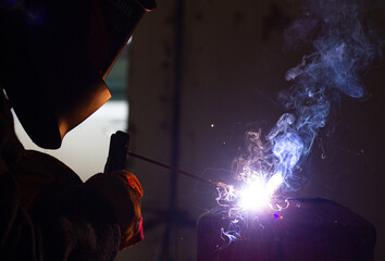 A welder in a workshop with a welding machine, welds metal structures. A worker in a factory uses a welding mask, tools and metalworking equipment.