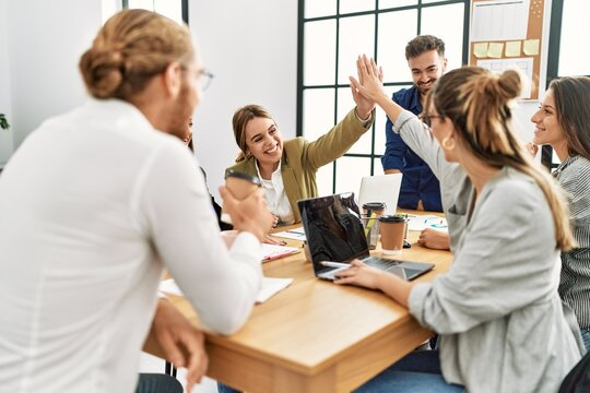 Two workers smiling happy high five during meeting at the office.