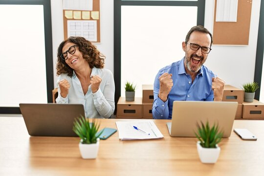 Middle age hispanic woman and man sitting with laptop at the office very happy and excited doing winner gesture with arms raised, smiling and screaming for success. celebration concept.