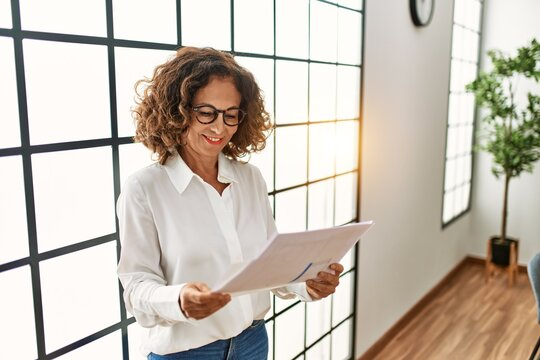 Middle age hispanic woman smiling confident working at office