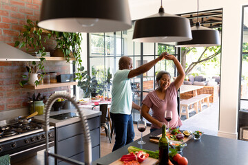 Happy african american senior couple dancing together in kitchen