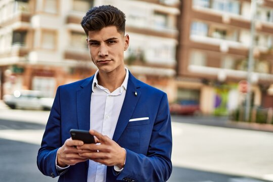 Young man using smartphone wearing suit at street