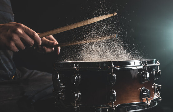 Close-up of a drummer playing a snare drum with splashing water.