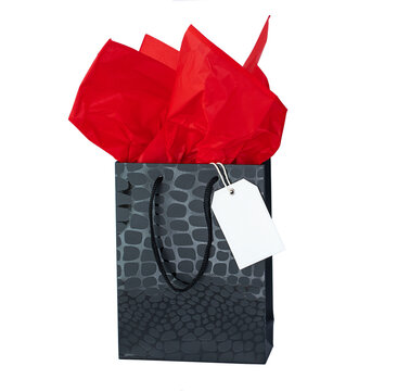Black gift bag with red tissue paper and white label isolated on white
