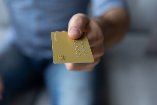 Crop close up young man holding showing gold credit card, giving at camera, customer paying for goods by debit card, shopping and purchasing, bank worker businessman offering service to client