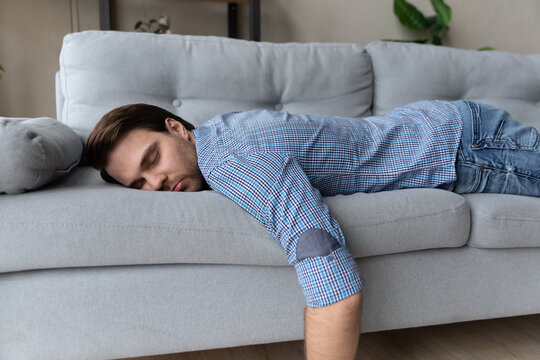 Exhausted man lying on comfortable couch at home, sleeping, taking day nap or daydreaming, tired overworked young male fall asleep on sofa after difficult working day, fatigue and tiredness concept