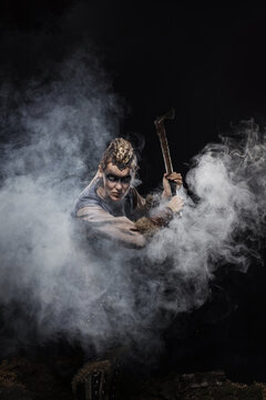 Woman viking warrior in history costume with ax aggressively attacks on dark background