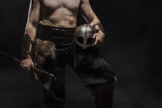 Close up viking warrior in full with ax on dark background
