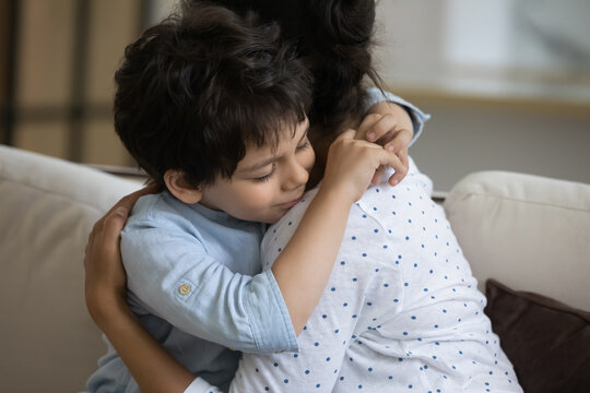 Adorable little kid son cuddling affectionate loving young indian mother, missing after long separation. Happy two generations asian ethnicity family showing tender feelings at home, family relations.
