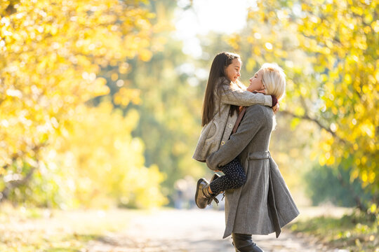Fashionable mother with daughter. Family in a autumn park. Little daughter in a coat.