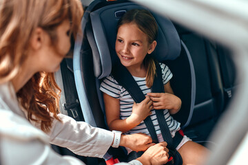Fototapeta A cute woman mother put her daughter in a car seat and fastens her seat belts. Protection during the trip in the car. obraz