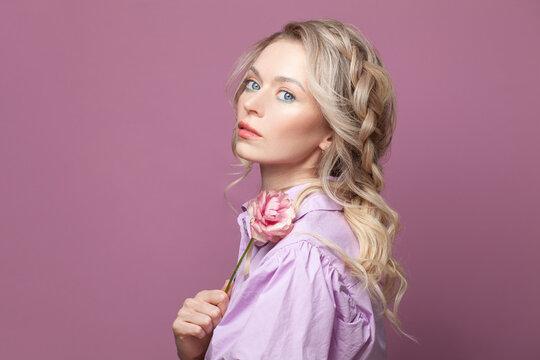 Attractive blonde woman on bright pink background portrait