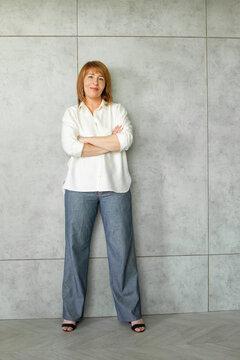 Beautiful positive businesswoman standing. Mature woman smiling