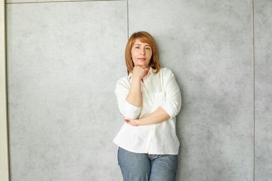Attractive redhead mature business woman in white shirt standing on grey background with copy space