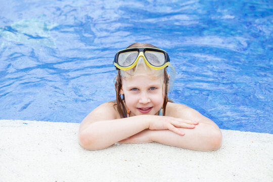 Smiling cute little child girl in pool