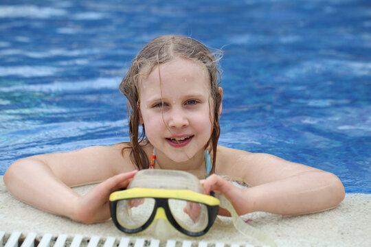 Child playing in pool. Little girl having fun in the pool. Summer holidays and vacation concept
