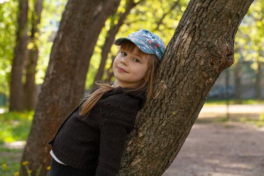 Outdoor portrait of a cute little 7 year old child girl wearing baseball cap near tree