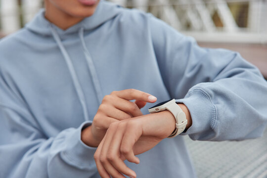Unrecognizable woman checks results of fitness training on smartwatch uses modern gadget dressed in blue hoodie poses outside looks at display monitors heart rate and pulse leads healthy lifestyle
