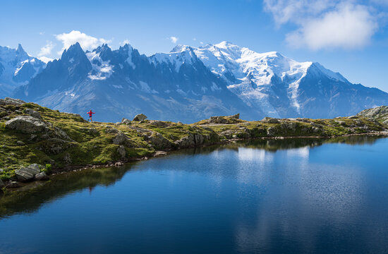 Female athlete trail running at Lac De Cheserys, with the Mont Blanc in the background.