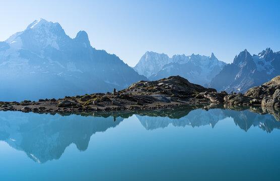 Woman enjoying the tranquil, morning view at Lac Blanc.
