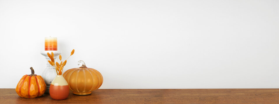 Autumn decor on a wood shelf against a white wall banner background. Pumpkins, candle and vase with fall colors. Copy space.