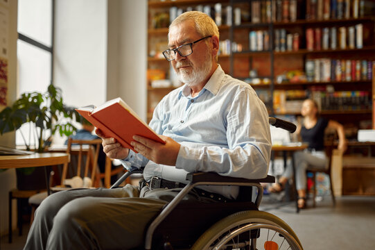 Adult disabled man in wheelchair reading a book