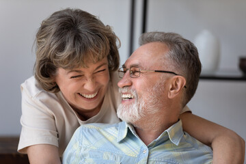 Obraz Head shot caring happy older woman cuddling joyful mature husband, laughing together at funny joke, enjoying pleasant conversation during carefree leisure weekend time at home, relations concept. - fototapety do salonu