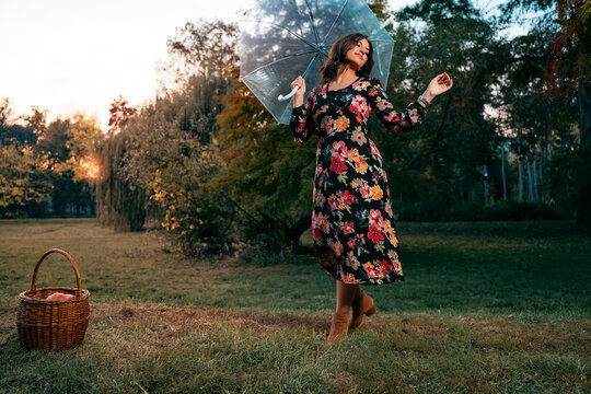 Gorgeous woman in floral dress posing with umbrella after the rain, autumn fashion portret