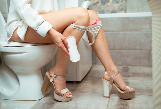 Unrecognizable woman sitting on toilet and holding hygiene pad in her hand. Woman personal hygiene