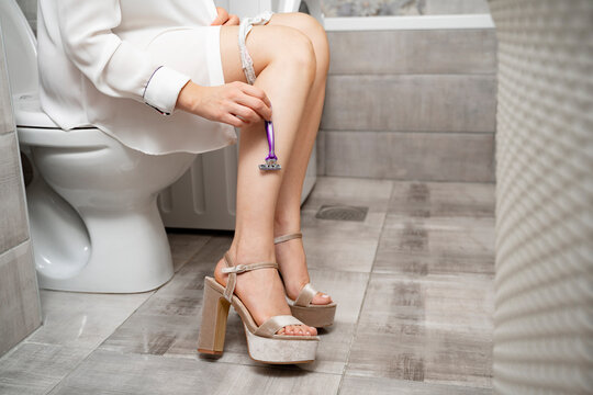 Woman sitting on toilet and shaving her legs with purple hand razor