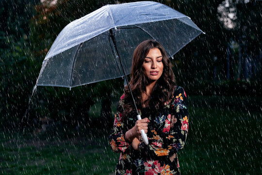 Beautiufl woman in floral dress on rainy autumn day. Beautiful woman with umbrella, pouring rain